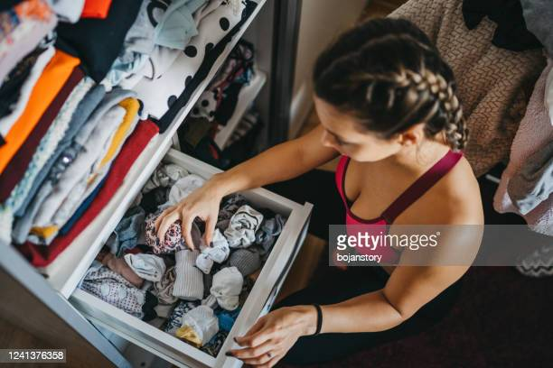 woman sorting out wardrobe - drawer stock pictures, royalty-free photos & images