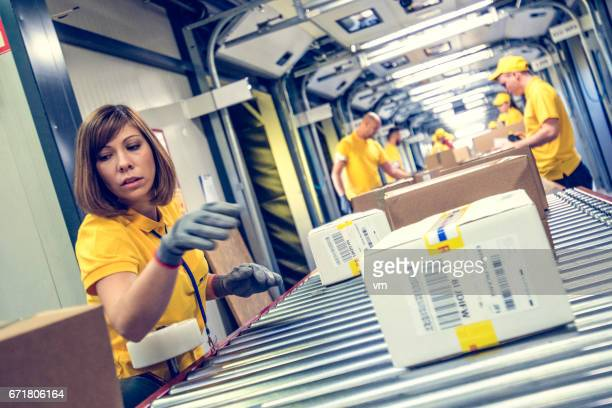 Woman sorting packages on a conveyor belt