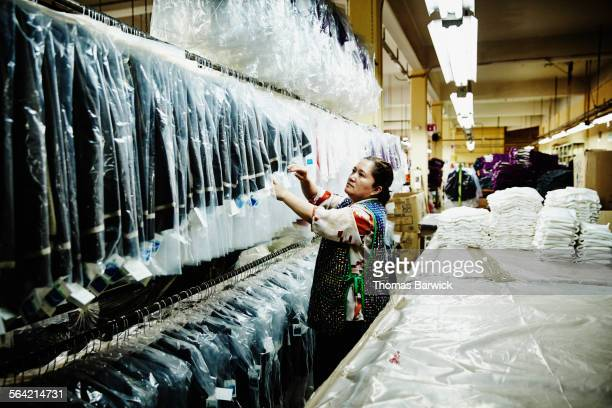 Woman sorting through row of jackets in factory