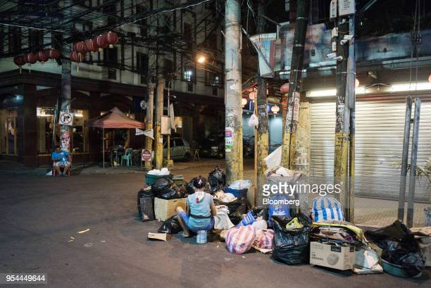 A woman sorts garbage in the street at night in the Chinatown area of Manila the Philippines on Wednesday May 2 2018 Home prices in the metropolitan...