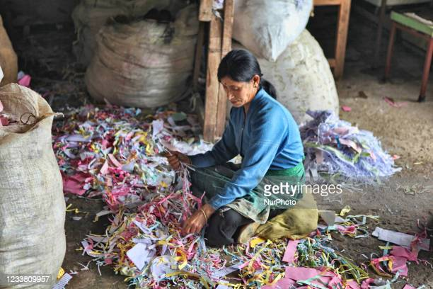 Woman sorts piles of scrap paper which will be recycled and made into new paper at the Cottage Industry in Gangtok, Sikkim, India. The Cottage...