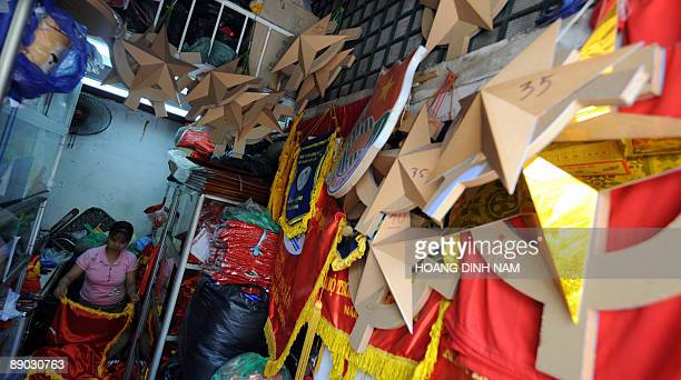 A woman sorts stuff out inside her tinny shop selling political decorative items including flags banners communist signs and portraits of Karl...