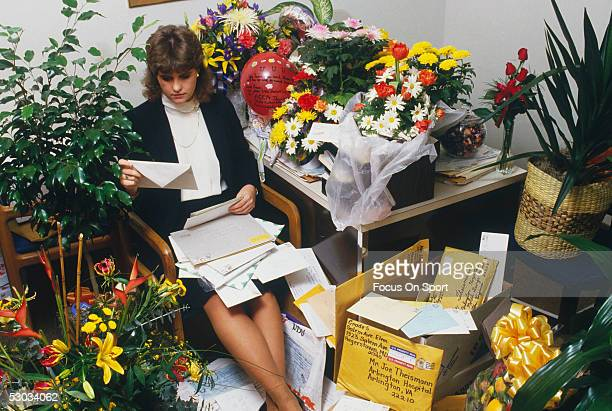 A woman sorts though a pile of gifts and cards sent to Washington Redskins quarterback Joe Theismann recuperating at Arlington Hospital after his...