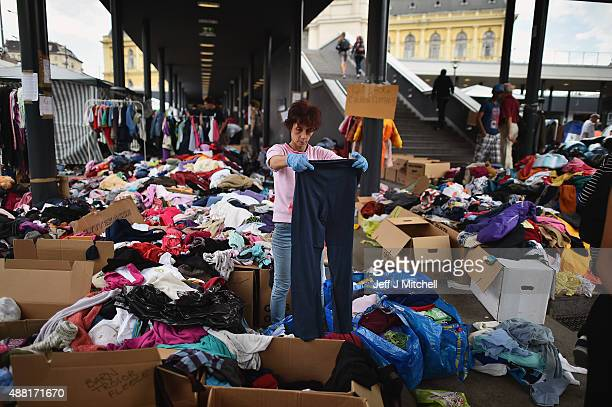A woman sorts through clothes at Keleti railway station on September 14 2015 in Budapest Hungary Migrants who arrive in Budapest overnight gather in...