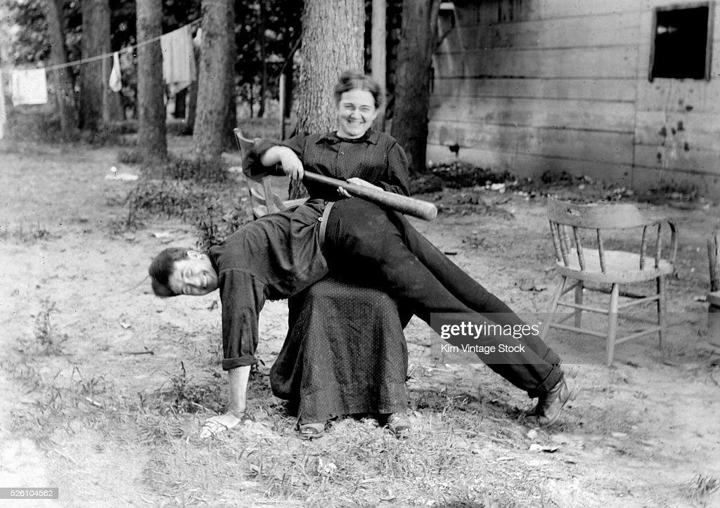 Woman spanks man with baseball bat playfully, ca. 1905 : News Photo