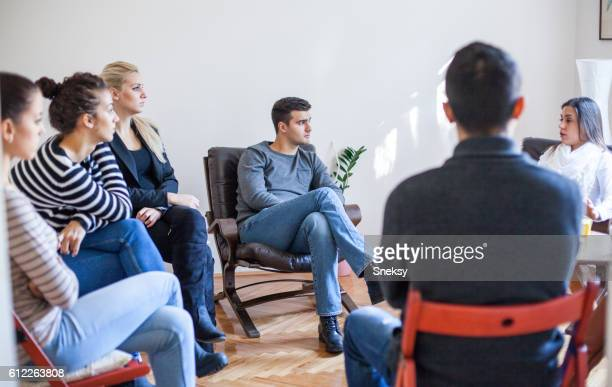woman speaking in group therapy session - community centre stock pictures, royalty-free photos & images