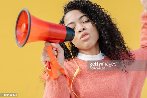 woman speaking on a megaphone while using headphones. - speech stock pictures, royalty-free photos & images