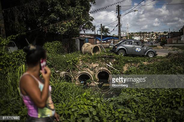 A woman speaking on a mobile phone looks toward an openair sewage system pouring into a local river in Recife Brazil on Wednesday Feb 17 2016 Zika...