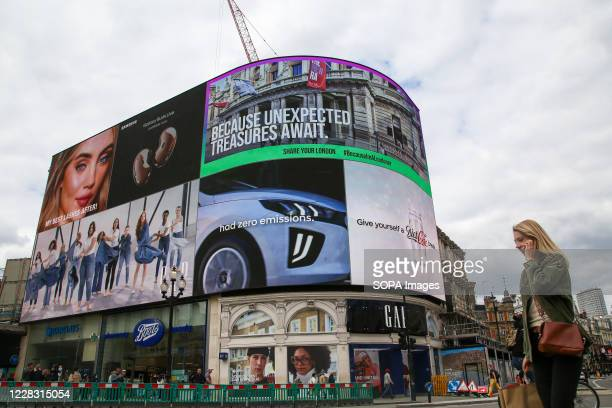 Woman speaking on her mobile phone walking past digital billboards at Piccadilly Circus in London's West End.