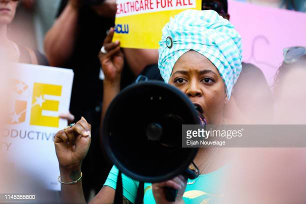 A woman speaks during a protest against recently passed abortion ban bills at the Georgia State Capitol building on May 21 2019 in Atlanta Georgia...