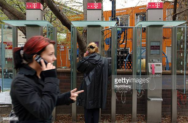 Woman speaks on a Deutsche Telekom pay phone as another passes speaking on a cell phone in Berlin, Germany, Monday, April 24, 2006. Blackstone Group...