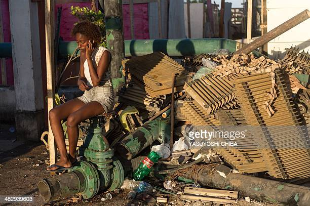 A woman speaks on a mobile phone after invading a deserted property belonging to a telephone company in Rio de Janeiro Brazil on April 4 2014...