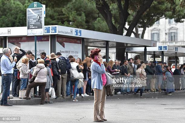 A woman speaks on a mobile phone as people wait at a bus station during a nationwide general strike of public workers started over the transportation...