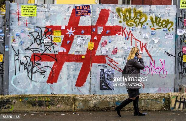 A woman speaks on a mobile phone as she walks past a graffiti covered wall with a giant hashtag sign near Moscow's Kursky railway station on November...