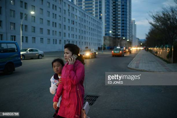 A woman speaks on a mobile phone as she walks with a child to watch a fireworks display during celebrations marking the anniversary of the birth of...