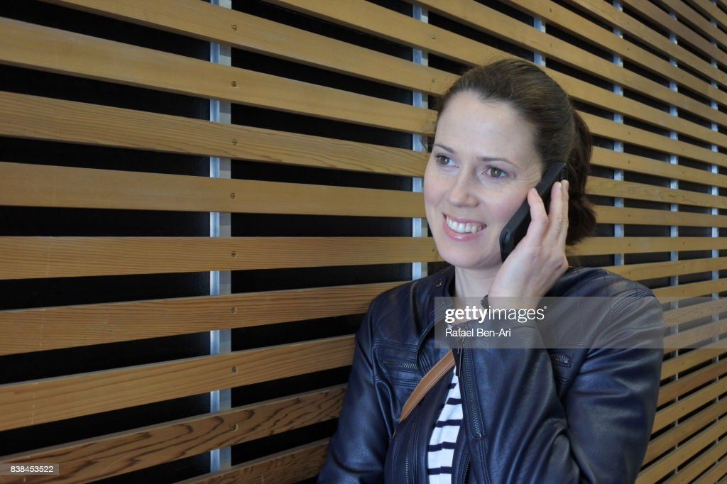 Woman speaks on a mobile phone : Stock Photo
