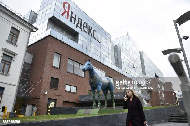 A woman speaks on her mobile phone as she walks outside the headquarters of Yandex company Russia's internet search engine in Moscow on May 16 2017...