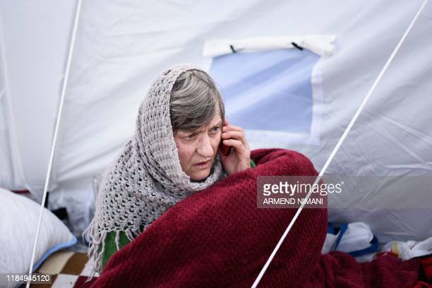 Woman speaks on her mobile phone at a makeshift camp at the soccer stadium in Durres, western Albania, on November 27 after the strongest earthquake...