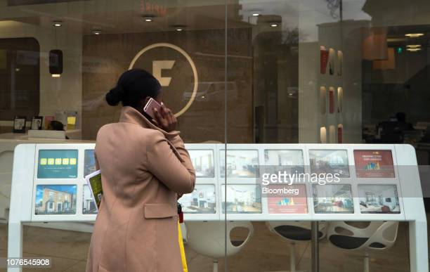 A woman speaks on her mobile phone while browsing properties displayed in the window of an estate agent in the Hackney borough of London UK on...