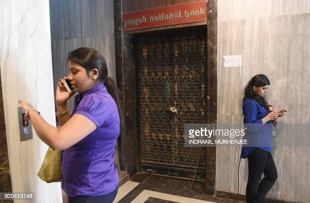 A woman speaks on her phone while a journalist waits next to the sealed entrance of the Brady House branch of the Punjab National Bank which had been...
