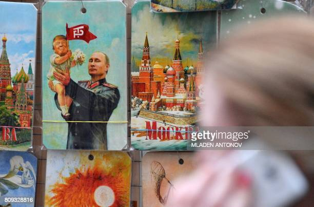 A woman speaks on the phone as she passes by a souvenir kiosk offering among others a drawing depicting Russian President Vladimir Putin holding a...