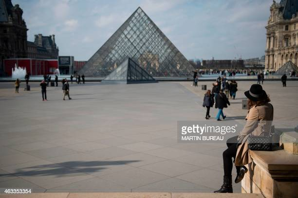 A woman speaks on the phone as she sits looking at the Louvre Museum's pyramid on February 13 2015 in Paris AFP PHOTO MARTIN BUREAU / AFP PHOTO /...