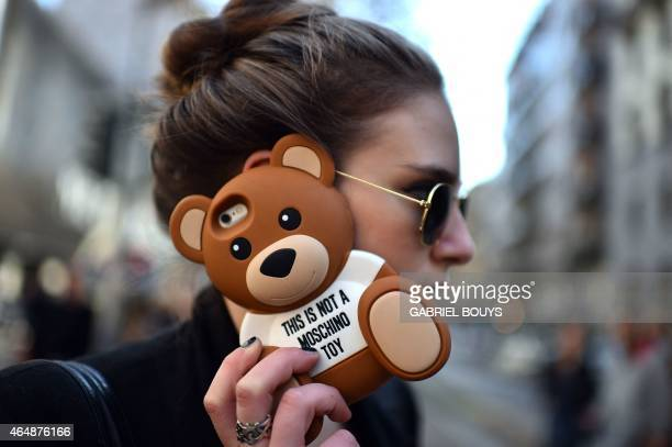 A woman speaks on the phone before the Dolce Gabbana fashion show during the women Fall / Winter 2015/16 Milan's Fashion Week on March 1 2015 AFP...