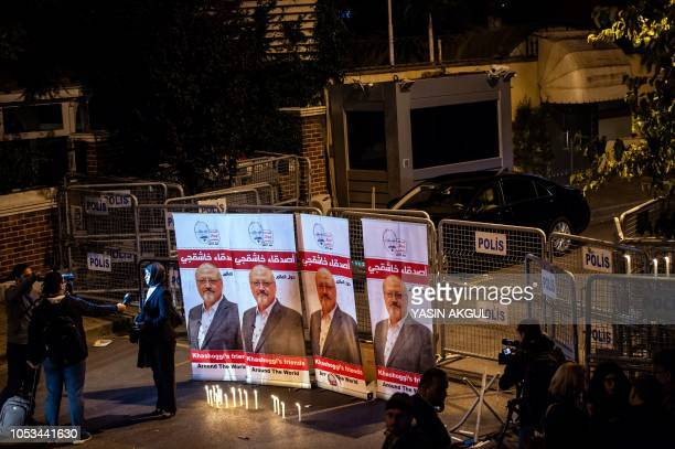 TOPSHOT A woman speaks to the press by a makeshifts memorial made of candles and posters picturing Saudi journalist Jamal Khashoggi during a...
