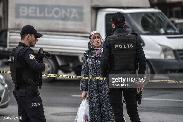 Woman speaks to Turkish police standing guard in front of the entrance of an underground car park, on October 23, 2018 in Istanbul, where an...