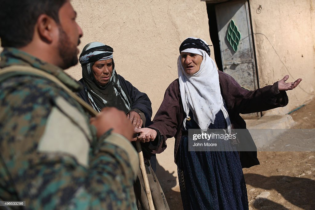 A woman speaks with an Arab member of the Syrian Democratic Forces after the village was liberated on November 10, 2015 near the ISIL-held town of Hole in the autonomous region of Rojava, Syria. A coalition of forces, primarily Kurdish, are attacking ISIL extremists in the area near the Iraqi border and calling in airstrikes from U.S.-led coalition warplanes. The autonomous region of Rojava in northern Syria has become a bulwark against the Islamic State. The Rojava armed forces, with the aid of U.S. airstrikes and weapons, are retaking territory which had earlier been captured much by ISIL from the Syrian regime.