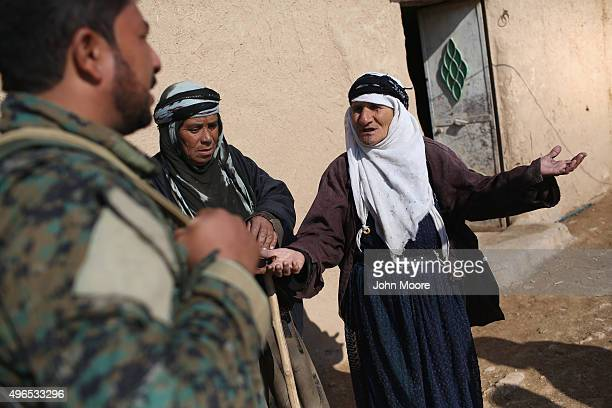 A woman speaks with an Arab member of the Syrian Democratic Forces after the village was liberated on November 10 2015 near the ISILheld town of Hole...