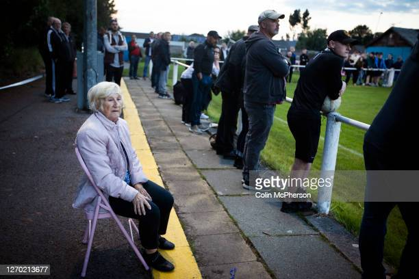A woman spectator seated watching the firsthalf action during the FA Cup Extra Preliminary Round between Daisy Hill and Colne at New Sirs...