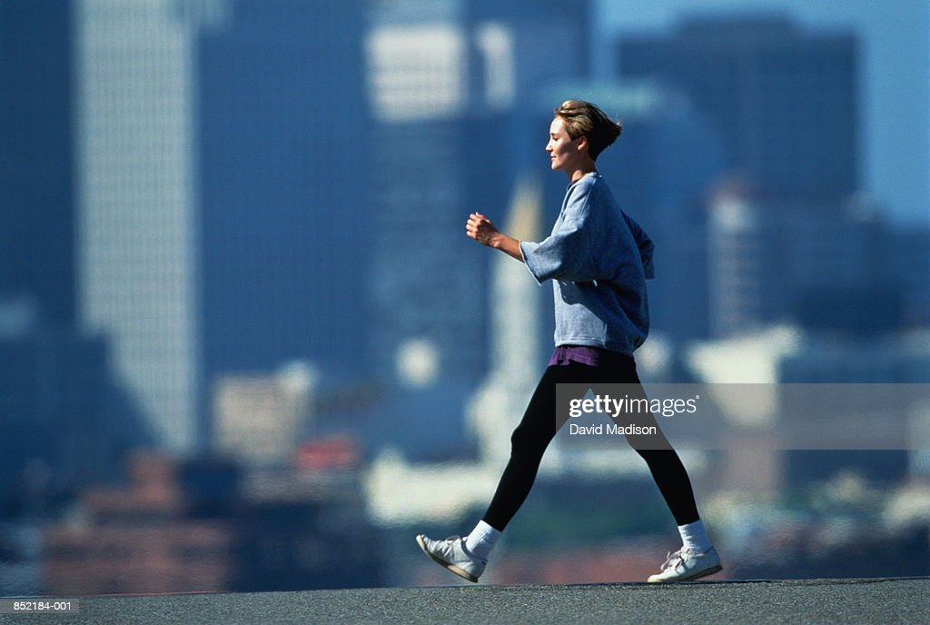 Woman speed walking in fore of city skyline : ストックフォト
