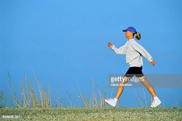 Woman speed walking, profile, against blue sky