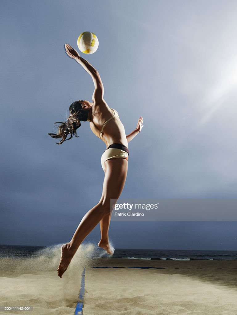 Woman spiking volleyball on beach, side view : Stock Photo