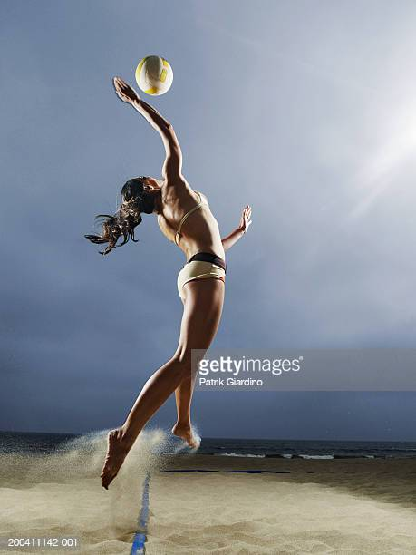 Woman spiking volleyball on beach, side view