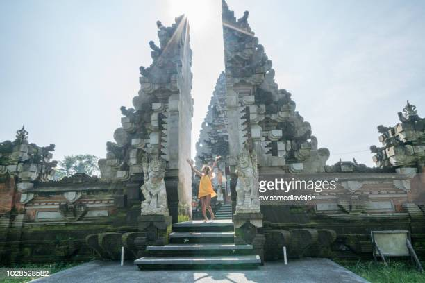 Woman spinning around dancing like happy girl in front of temple's entrance at gate in Ubud, Bali- Indonesia- People travel destinations fun lifestyles concept