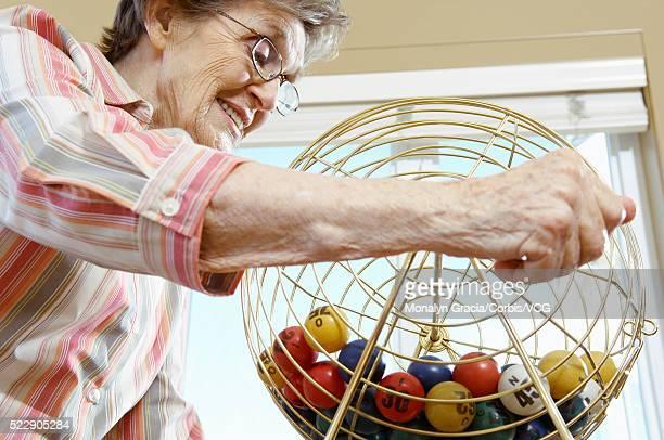 Woman spinning bingo ball dispenser