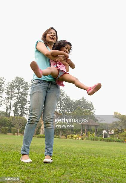 Woman spinning her daughter in a park