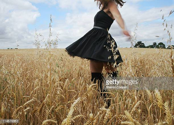 woman spinning in field of ripe wheat on sunny day - letchworth garden city stock photos and pictures