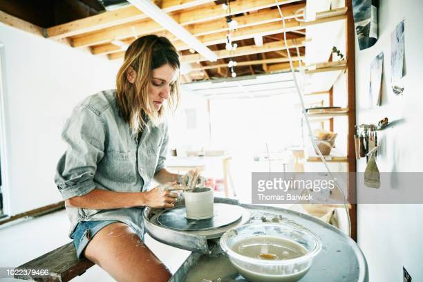 woman spinning mug on potters wheel in garage studio - リアルライフ ストックフォトと画像