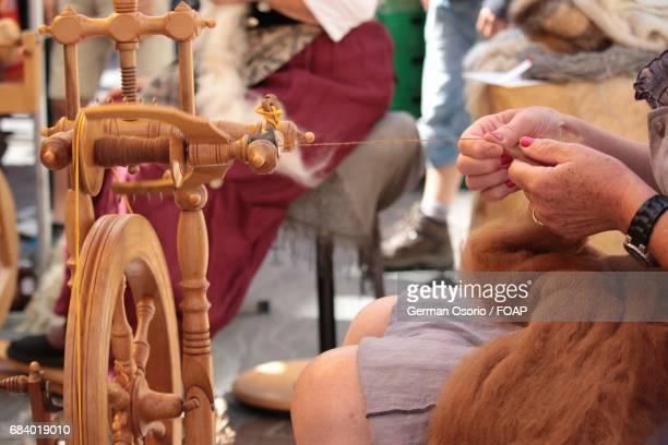 Woman spinning wheel to make yarn