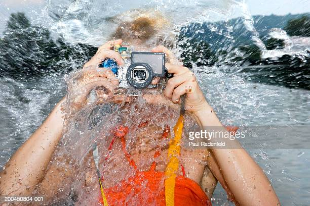 Woman splashed with water as she photographs with underwater camera