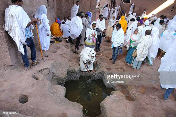 A woman splashes herself with holy water at Beta Mariam Church on January 7 2016 in Lalibela Ethiopia Thousands of adhearants to the Ethiopian...