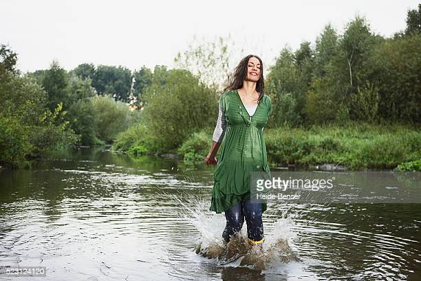 woman splashing in a river - wet jeans stock photos and pictures