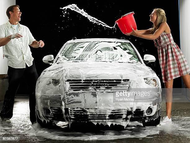 Woman splashing Man while washing car