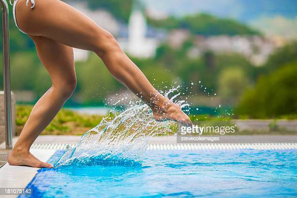 Woman Splashing The Pool Water With Her Foot