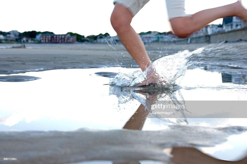 Woman splashing through tide pool on beach : Stock Photo