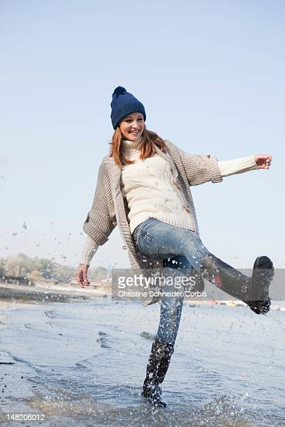 woman splashing water at lakeshore - gummistiefel frau stock-fotos und bilder