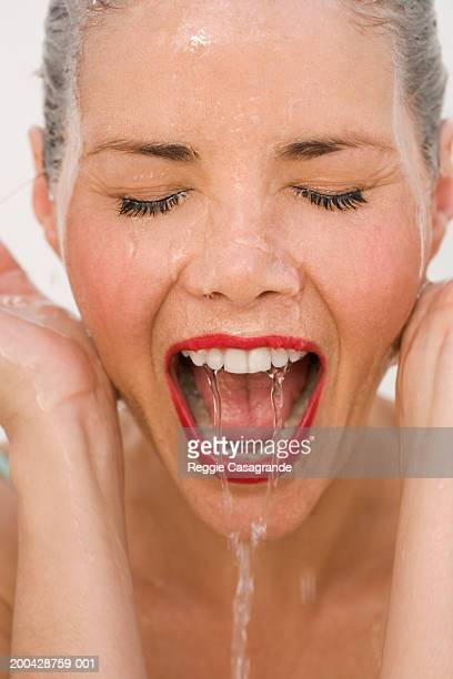 Woman splashing water on face, eyes closed, mouth open